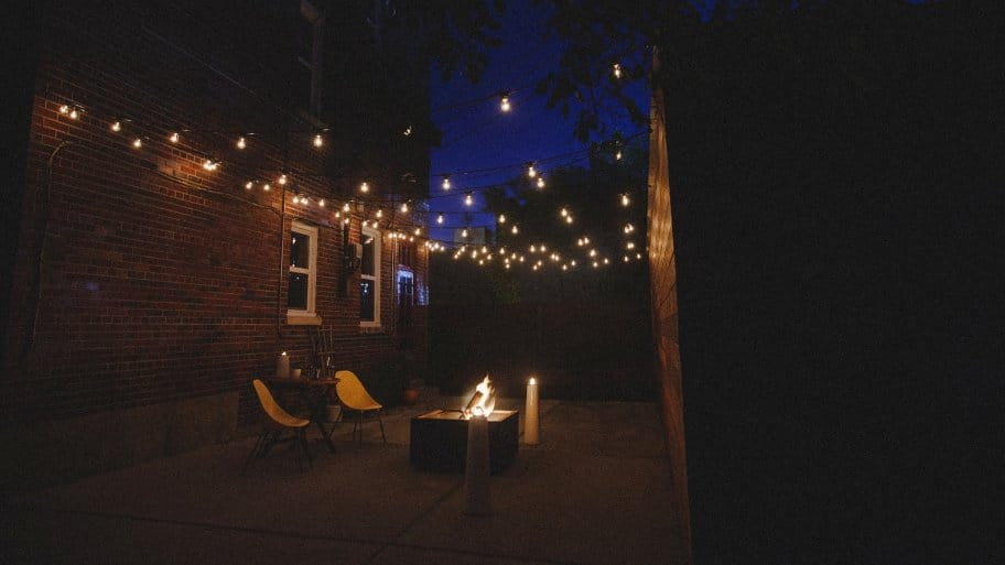 patio at night with fire pit and string lights