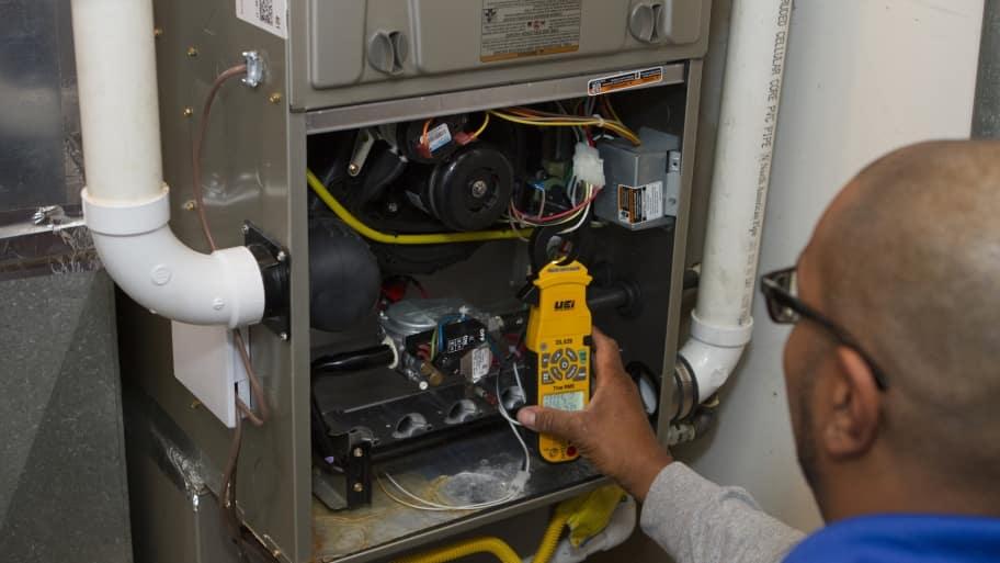 furnace technician performs HVAC repairs