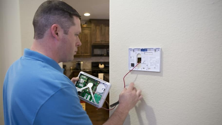 home security technician working on install