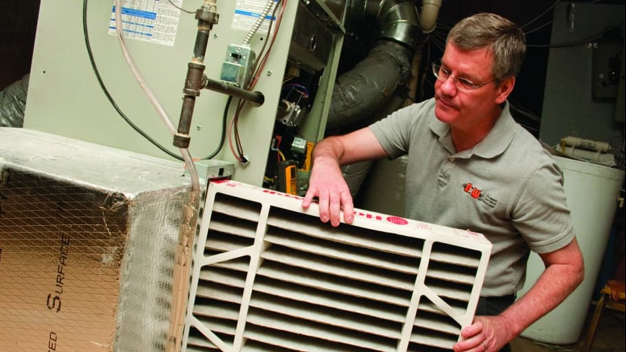 HVAC technician installing furnace air filter