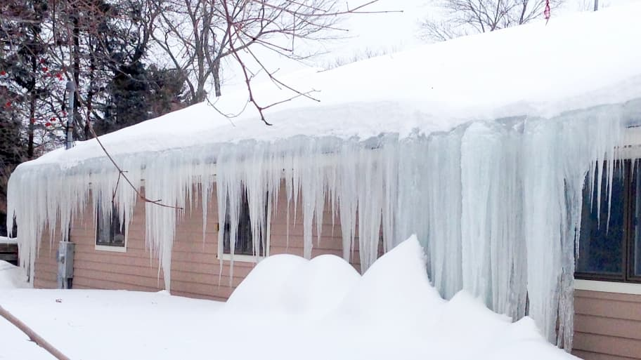 big icicles hang on ranch house with snow on roof