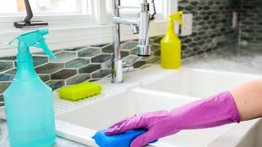 cleaning kitchen sink in purple gloves