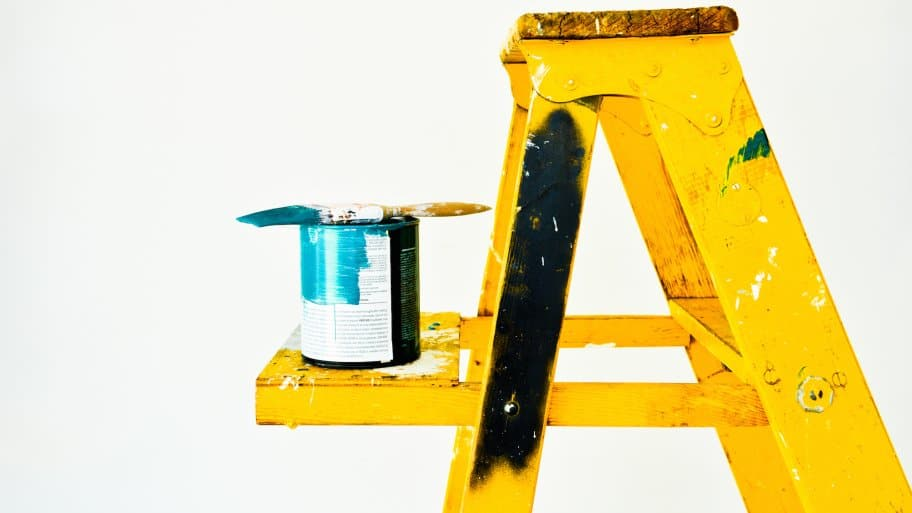 yellow ladder with paint and paintbrush