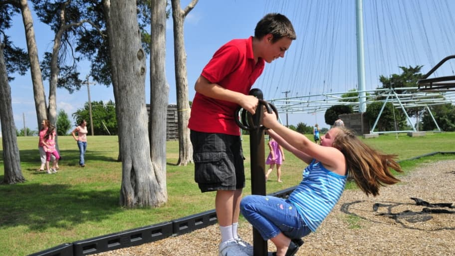a young boy and girl play together on a playground