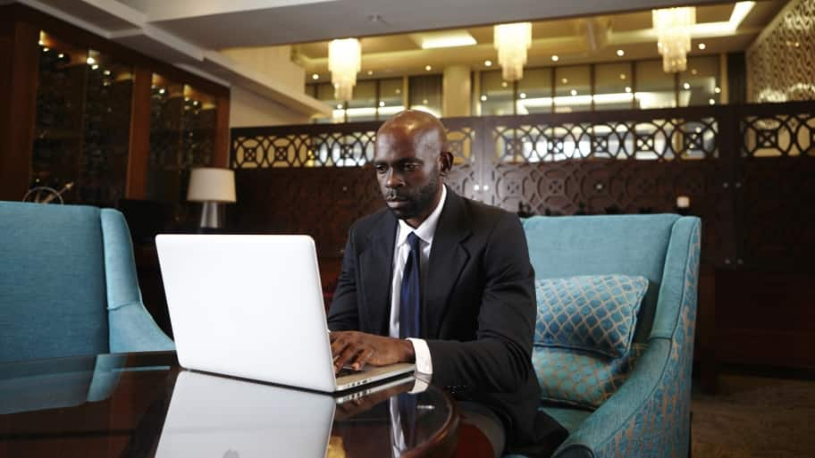 man on computer in hotel lobby