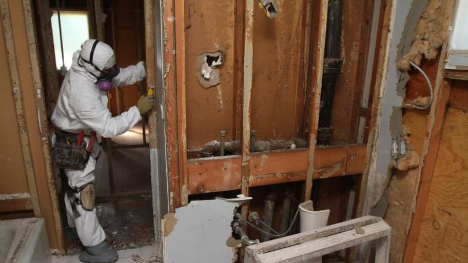 A man in a mold remediation uniform removes drywall from a bathroom to clear mold out of a home.
