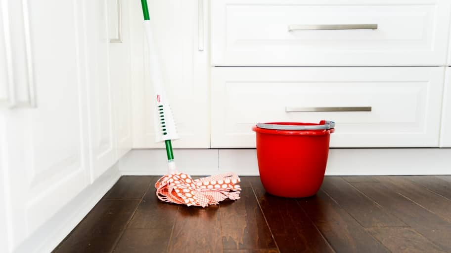 mop and red bucket on wood floor (Photo by Summer Galyan)