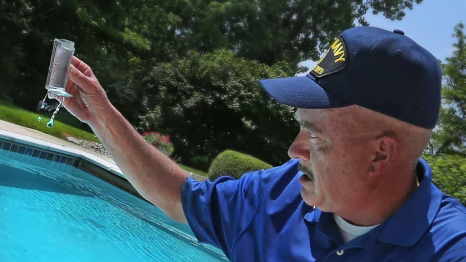 A pool cleaner checks chemicals