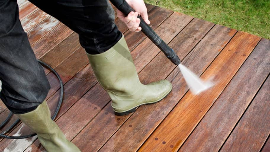 Pressure washer cleaning a deck