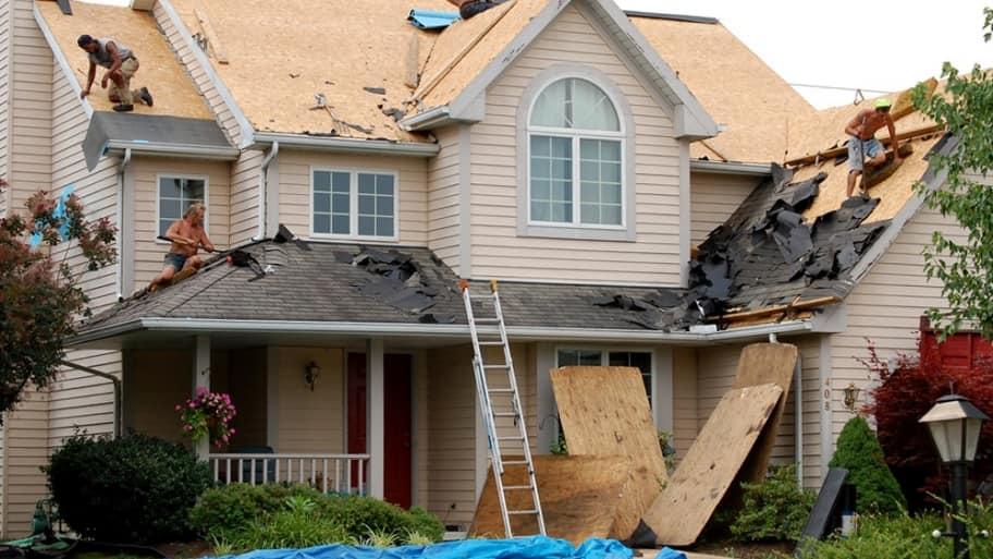 roofers tearing off old asphalt shingle roof