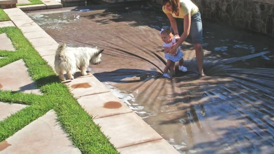 a child and mother walking on a swimming pool's child-proof safety cover
