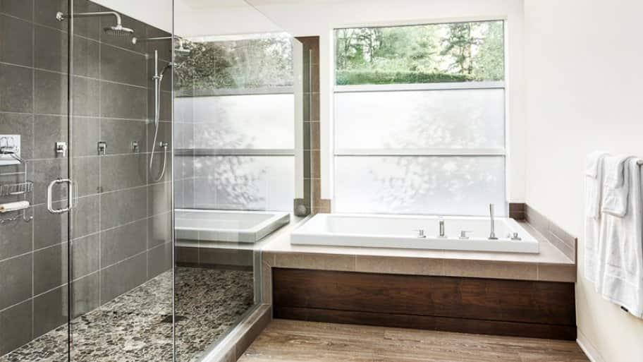 Large glass shower with gray tile, alongside bathtub with wood base