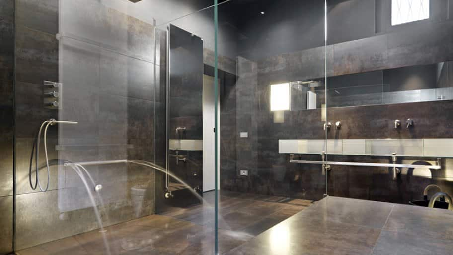 Stone shower with multiple shower heads and chrome hardware