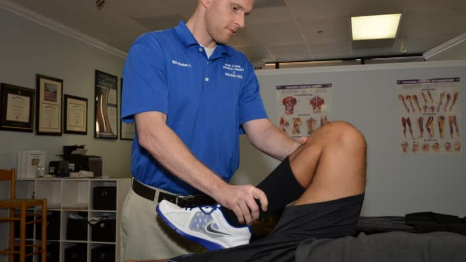 A physical therapist stretches a leg