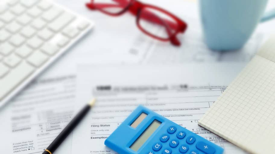 calculator and pen with some tax forms