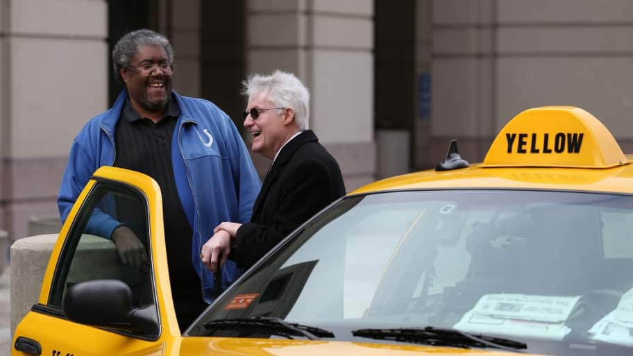 yellow cab driver helps passenger out of taxi