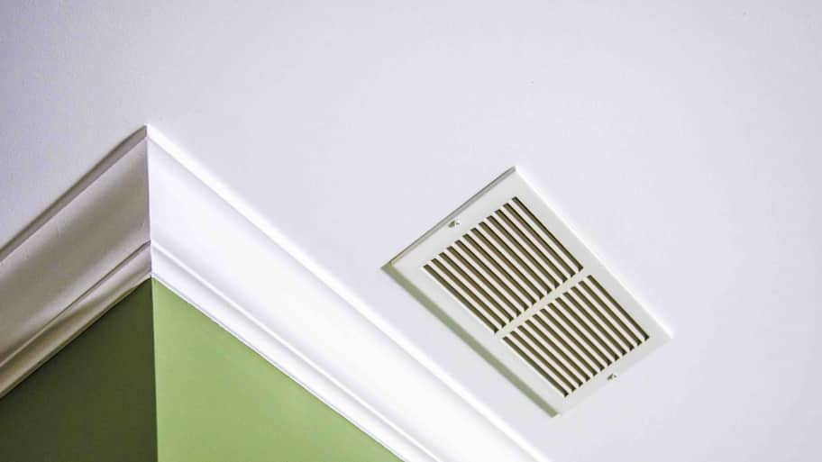 white ceiling with crown molding and air vent