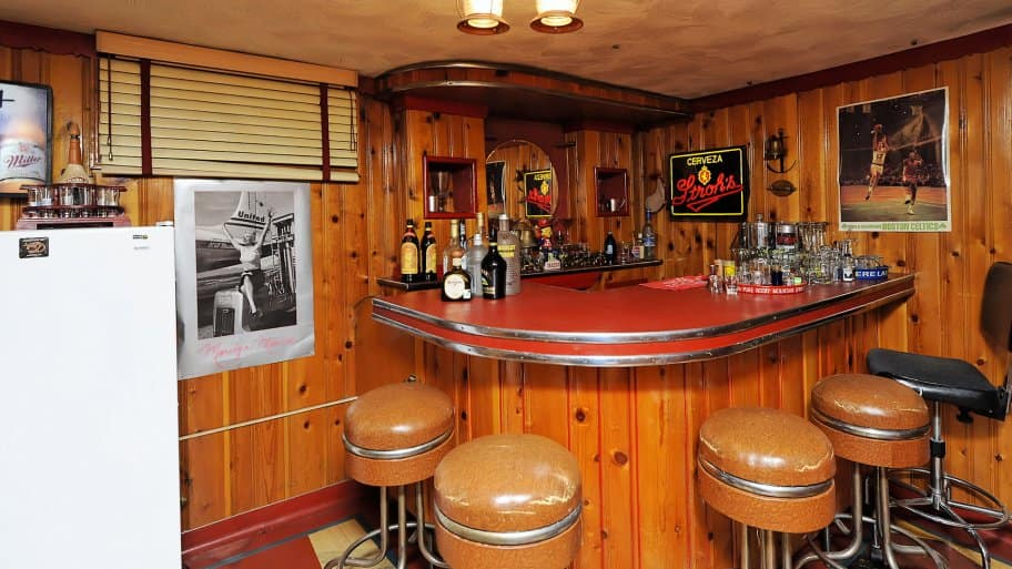 basement man cave with dark lighting, wood panels, alcohol ads and bar stools.