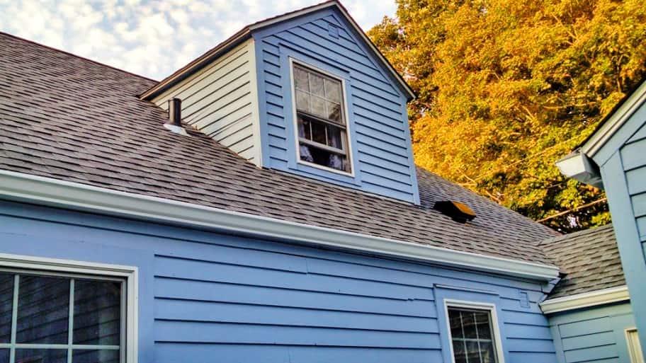 blue house with asphalt roof shingles