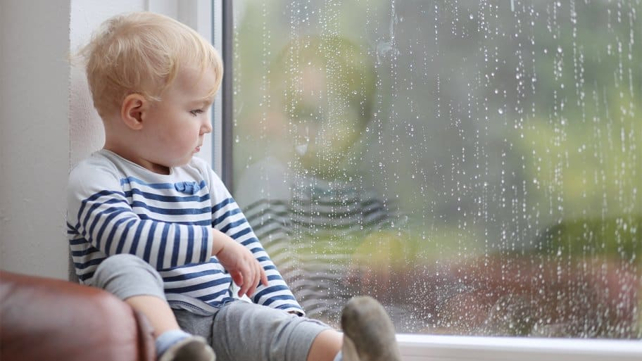 A baby watching rain out the window