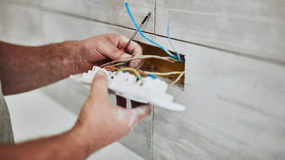 Electrician fixing wires of an outlet (Photo by Astrosystem - stock.adobe.com)