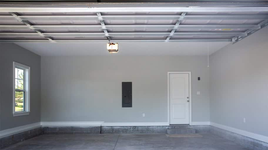 Empty two car garage with door leading inside home