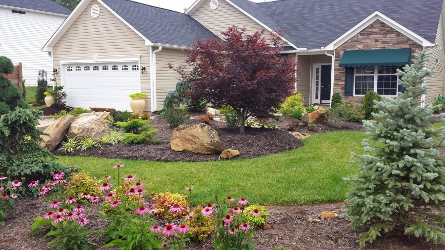 Home with landscaping featuring boulders, evergreens and flowers.