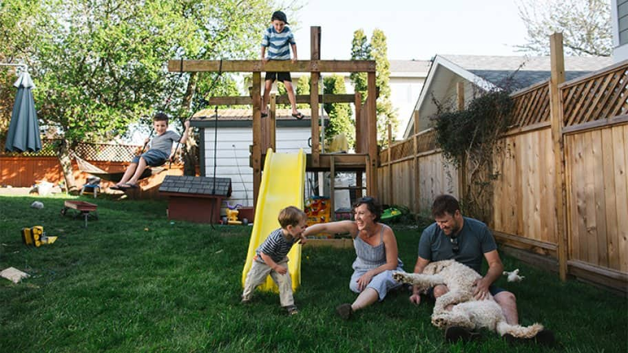 Family playing on a backyard playground and swing set