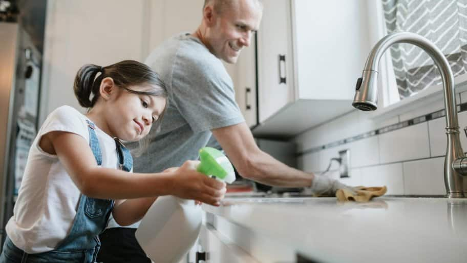 A father and his daughter cleaning their kitchen sink