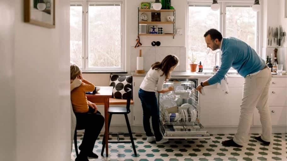 Father and daughter arranging utensils in dishwasher while standing at kitchen