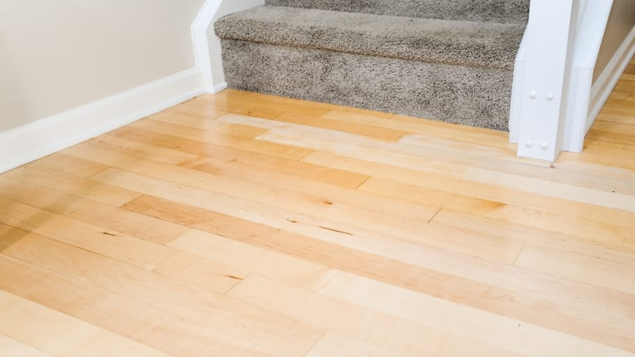 hardwood floor at bottom of carpeted stairs