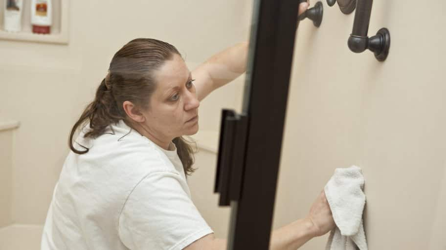 housekeeping company employee cleanign a shower