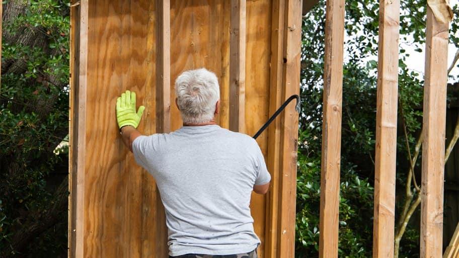 Man taking apart walls of house