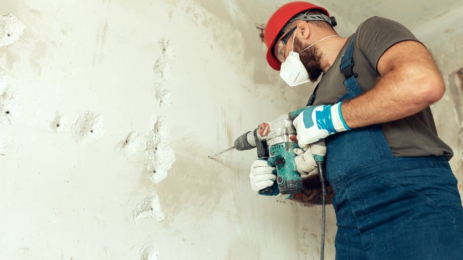 Professional preparing concrete wall to be demolished