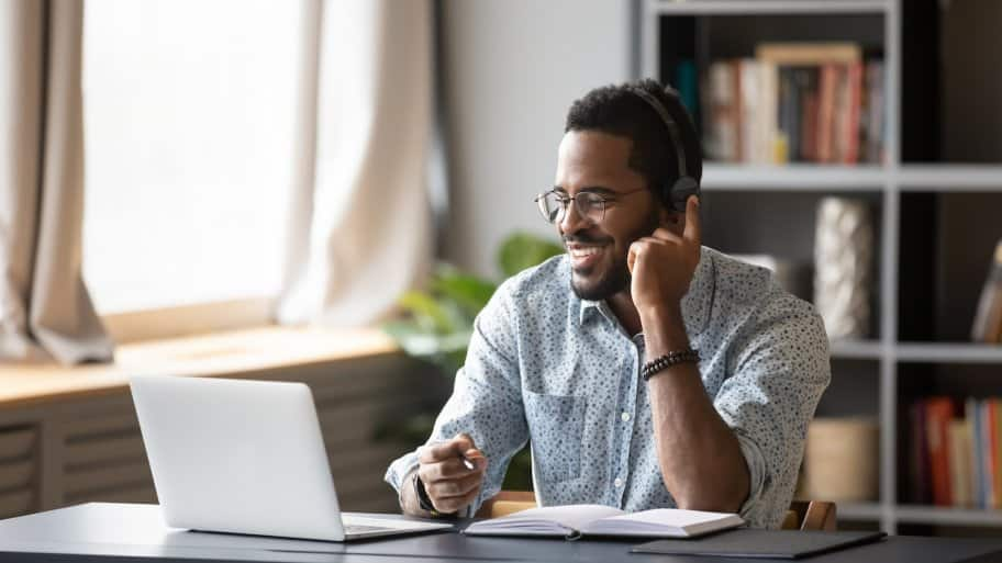 Man working from home in modern home office with glasses, headphones and a collared shirt