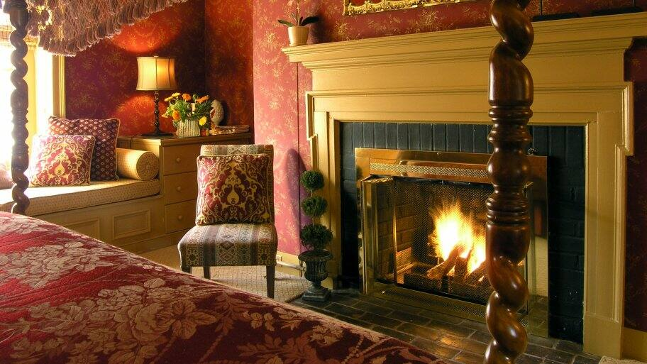 master bedroom with chair and fireplace