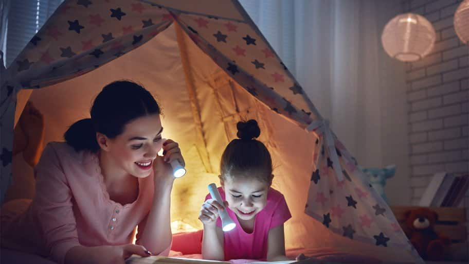 Mom and daughter reading by flashlight (Photo by Choreograph via Getty Images)
