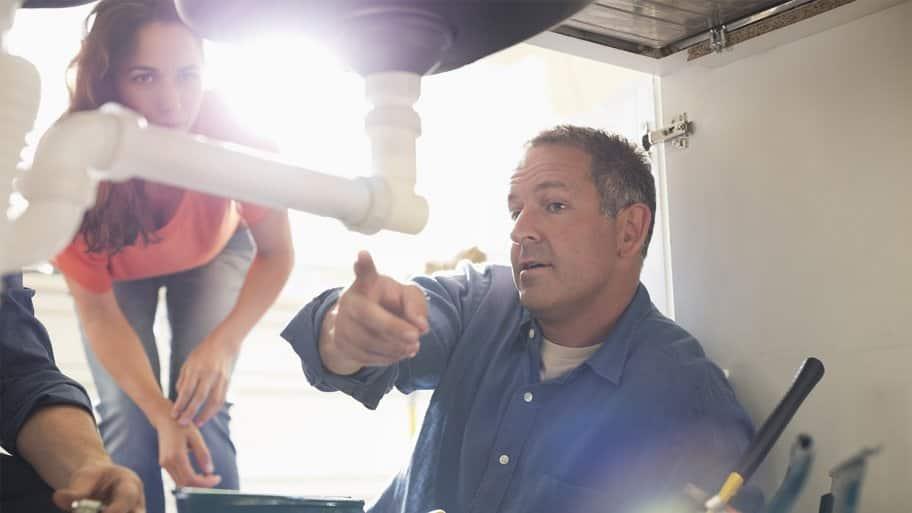 Plumber explaining pipe repair to homeowner