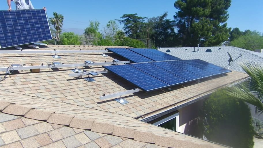workers on roof installing solar panels