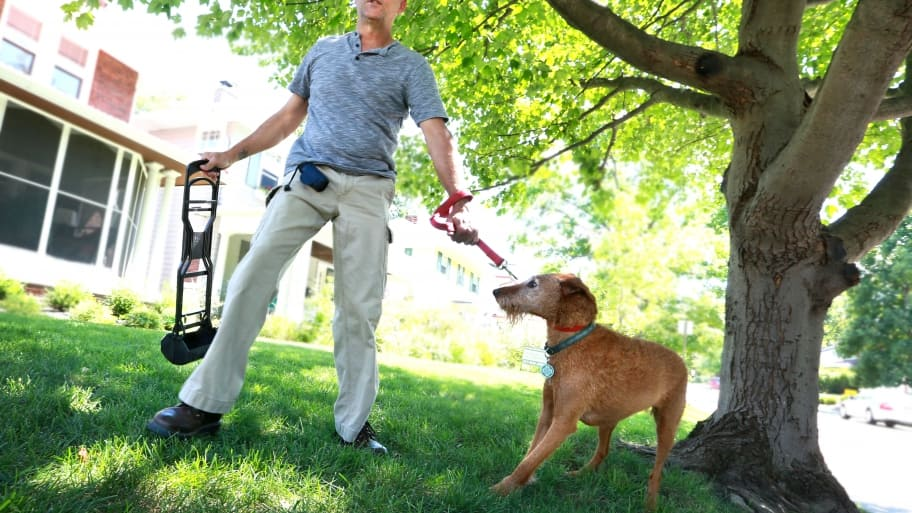 man with pooper scooper and dog