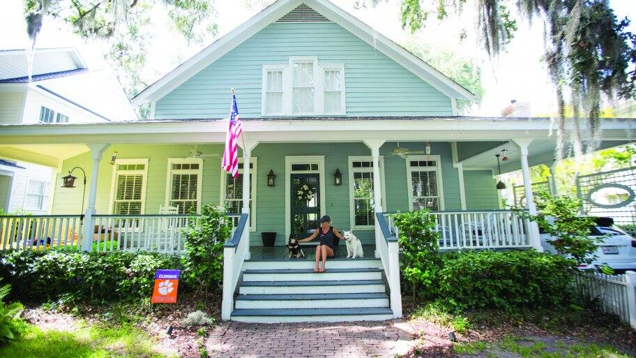 Savannah home with owner and dogs on front porch