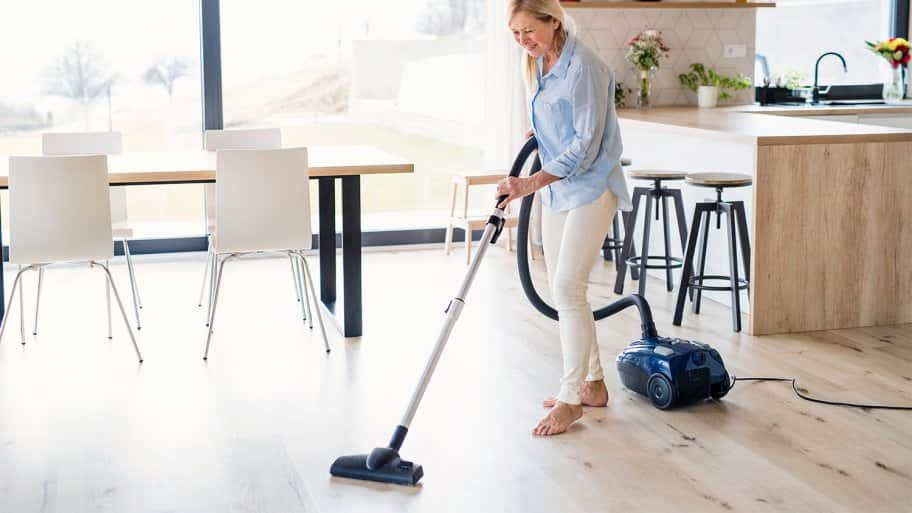 Woman vacuuming wood floor of home dining area