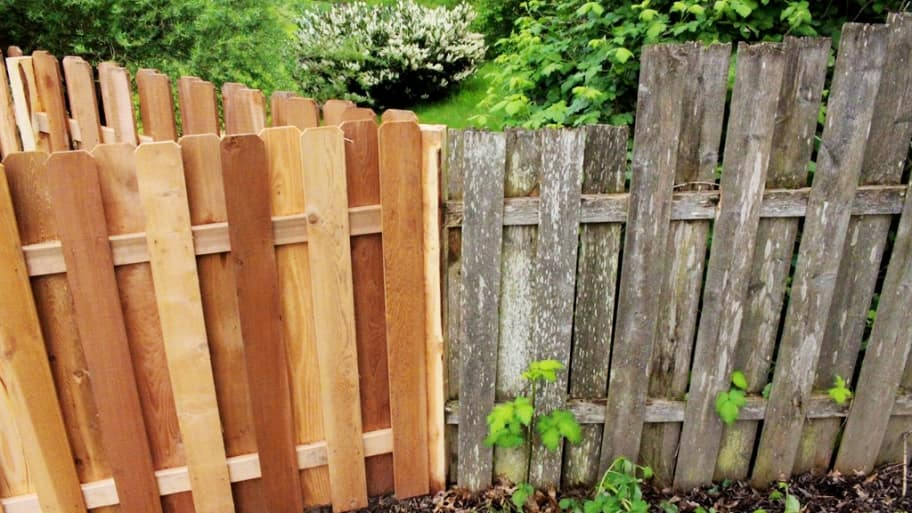 Gray old fence next to fresh new fence