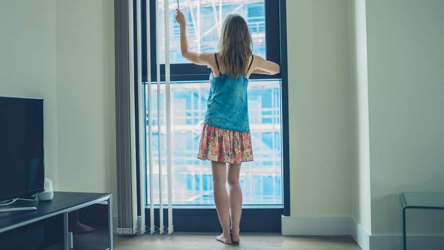 Woman closing blinds in apartment