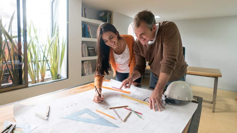 A couple of architects working on a blueprint at their office