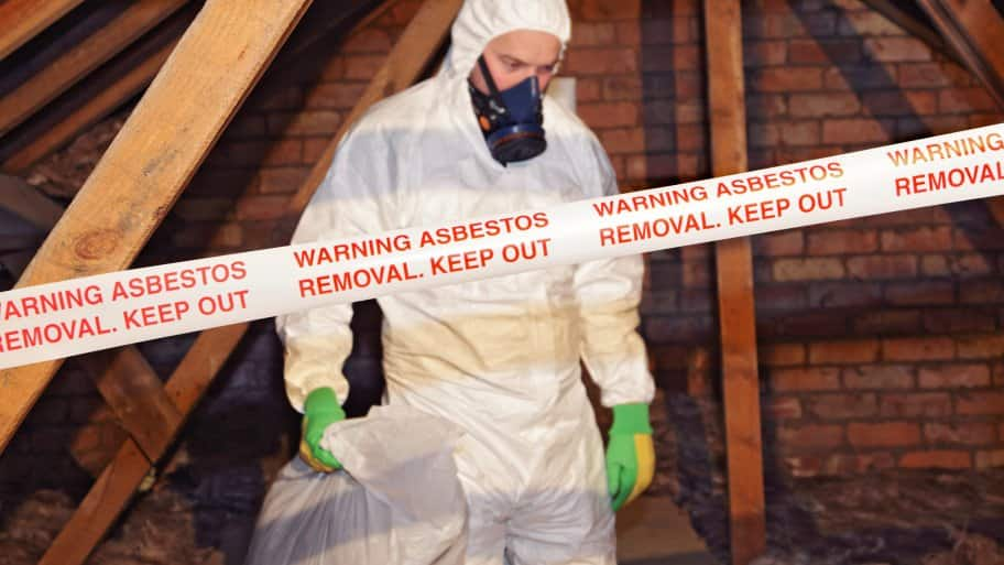 Man in hazmat suit removing asbestos from attic (Photo by GettyImages)