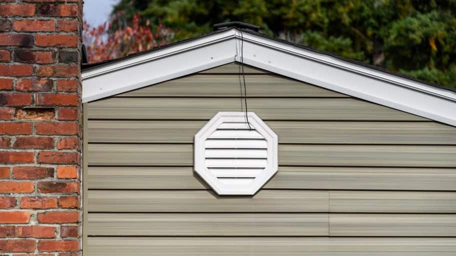The exterior wall of a house with an attic fan (Photo by knelson20 - stock.adobe.com)