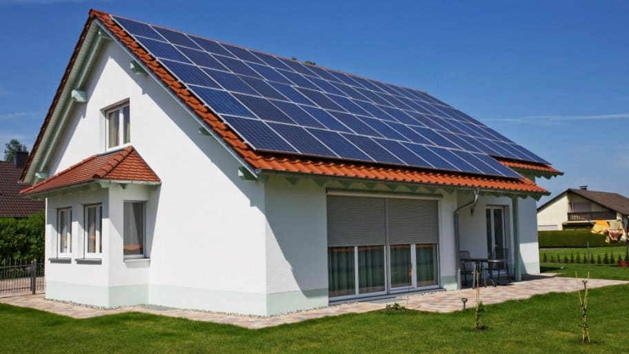 a house with brick shingles and solar panels