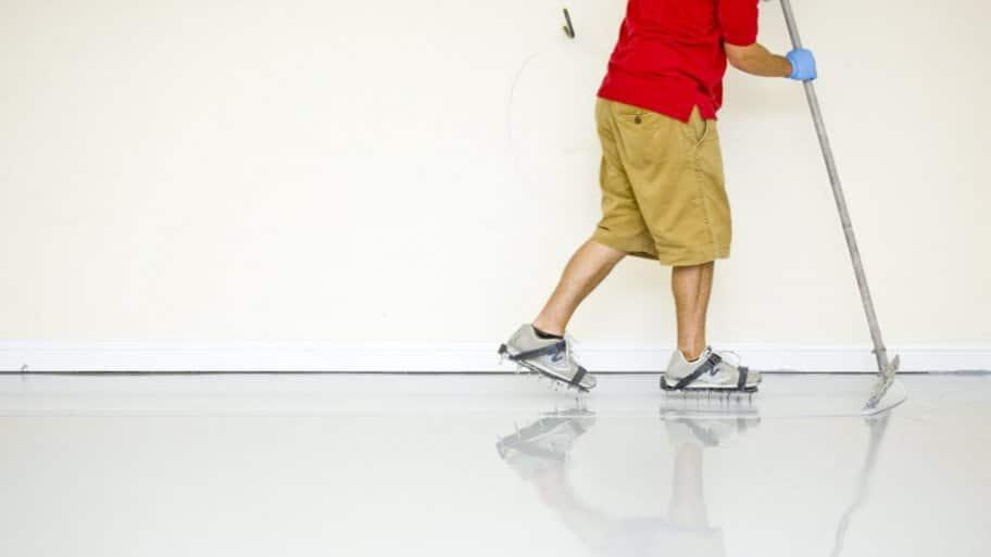 Man applying epoxy sealant to floor