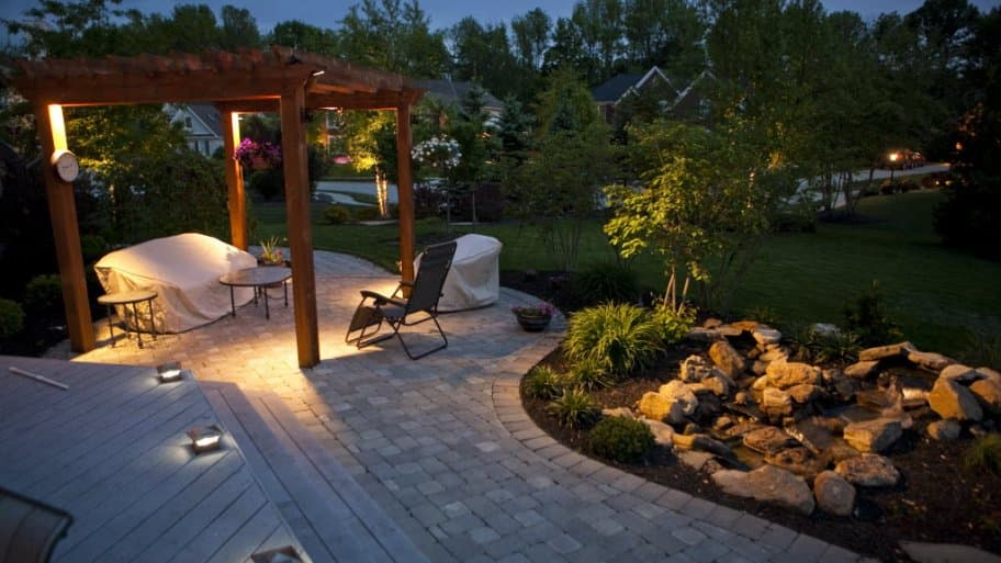 a back yard with a gazebo, rocks, trees and outdoor lighting